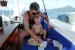 Maria reading a book to Keanu while sailing